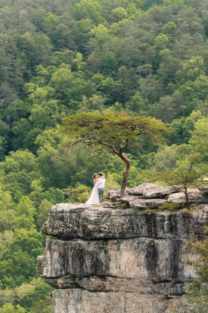 Mountain elopement, Tennessee. The couple enjoy their first dance on a cliff with thick green forest behind.