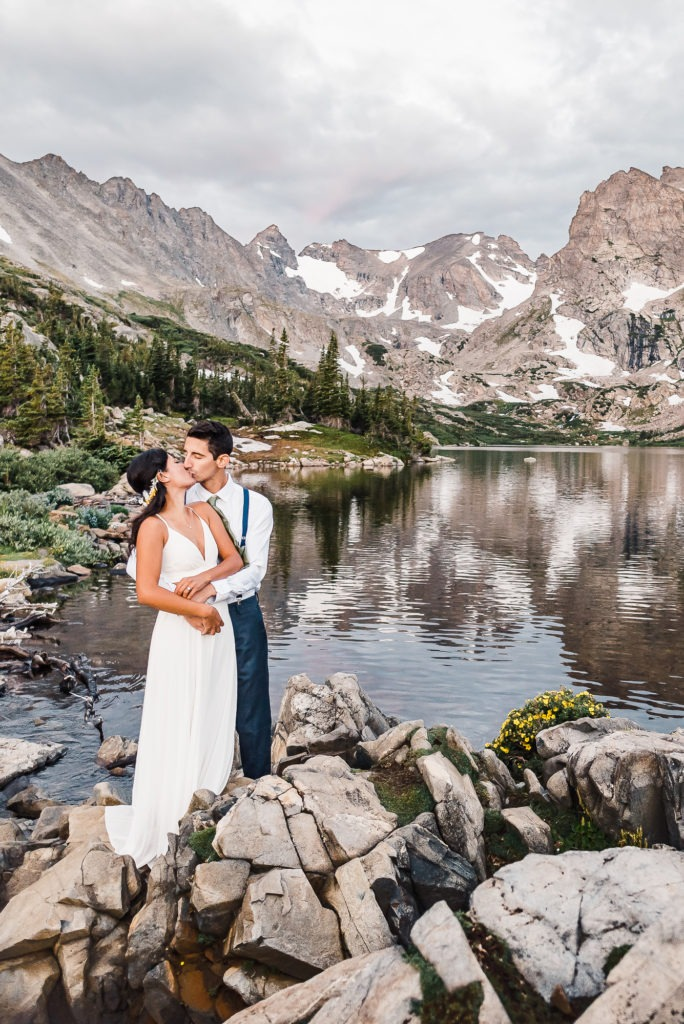 Colorado mountain elopement. The couple share a kiss on the edge of a pristine alpine lake.
