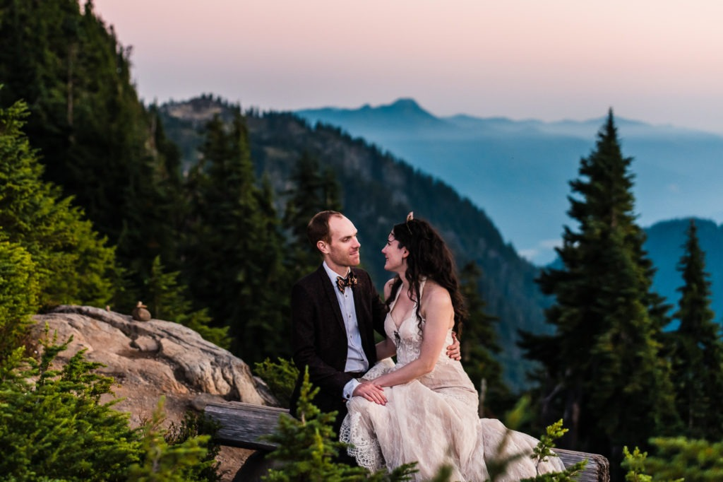 North Cascades, Washington elopement. The couple cuddle together sitting on a wooden bench overlooking lush forest and misty mountains. They're a striking, alternative couple: he is in a brown suit and metallic bow tie, she has a crystal crown and jewelled headpiece.