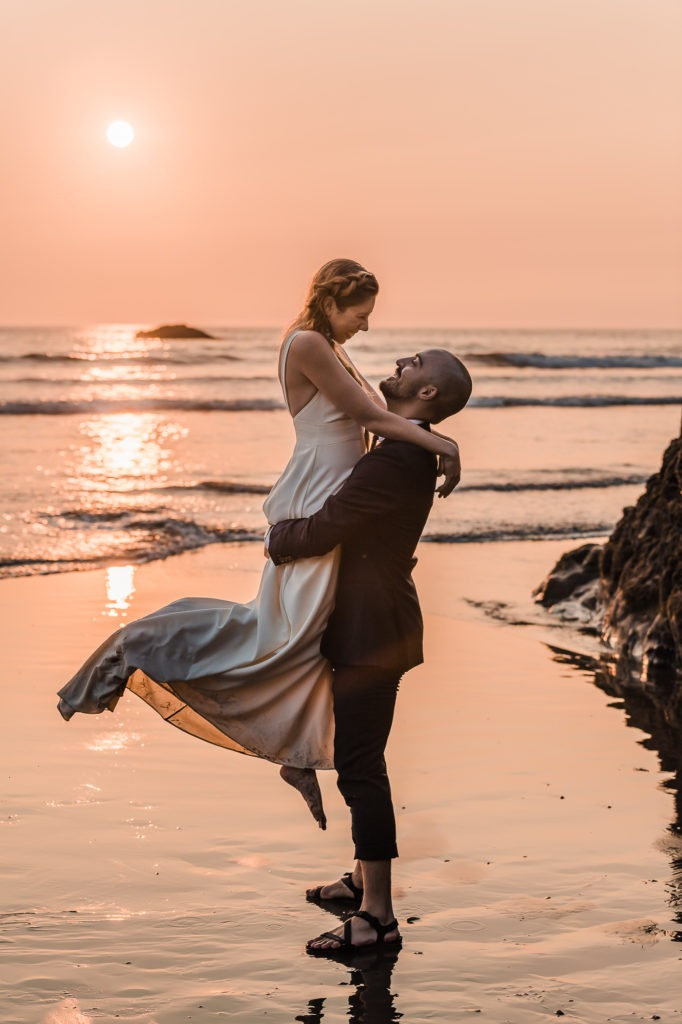 Olympic National Park elopement. At this Washington sunset elopement, the couple share a dance in the shallow waves, and the groom lifts his bride high in the air as the sun casts a pink glow on the scene.